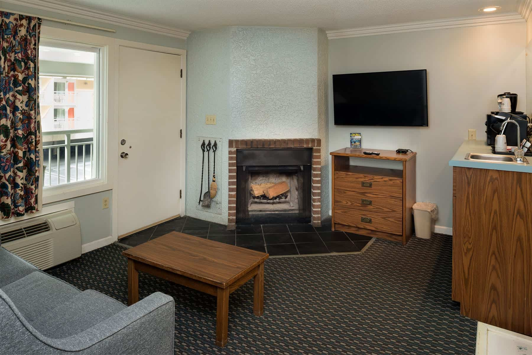 Suite with couch, fireplace, and coffee bar